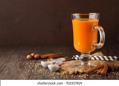 Pumpkin carrot fresh smoothie with cinnamon and spices on old rustic wooden table. Selective focus, Copy space. Autumn concept