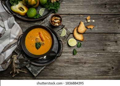 Pumpkin and carrot soup with baked peppers and cheese, lime juice and ginger in black plate over dark background Top view Copy space.