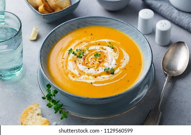 Pumpkin and carrot soup with cream on grey stone background.