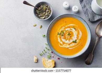 Kürbis und Karottensuppe mit Sahne auf grauem Hintergrund. Kopiert Platz. Draufsicht.