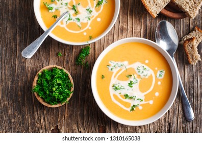 Pumpkin and carrot soup with cream and parsley on wooden background. Top view.