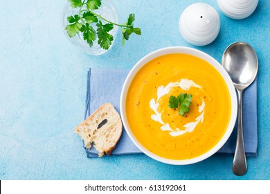 Pumpkin and carrot soup with cream and parsley on blue stone background. Top view. Copy space
