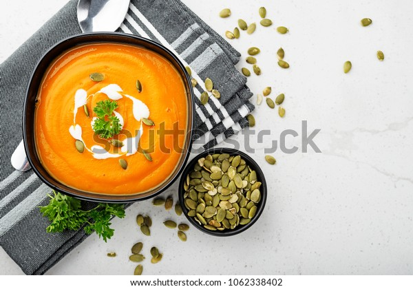 Pumpkin and carrot soup with cream and parsley on gray background. Top view