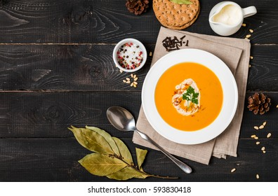 Pumpkin and carrot soup with cream and seasoning in white bowl  on black wooden background, top view