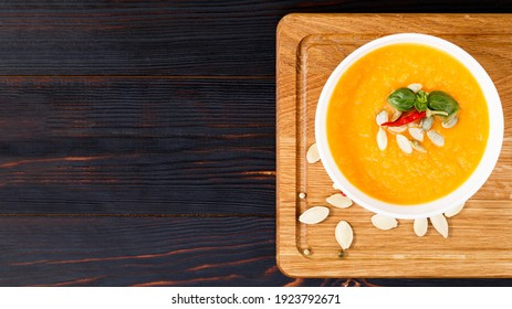 Pumpkin and carrot soup with cream and pumpkin seeds on wooden background with copy space. Top view.
