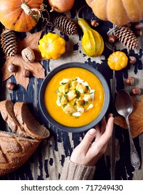 Pumpkin or carrot soup with croutons and herbs in a woman's hand. Vegetable harvest autumn background. Autumn meal food. View from above. Flat lay with autumn vegetables.