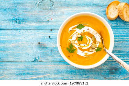 Pumpkin and carrot soup with parsley on blue background Top view.