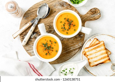 pumpkin or carrot or sweet potato vegetable soup in white bowls served on a light background, top view