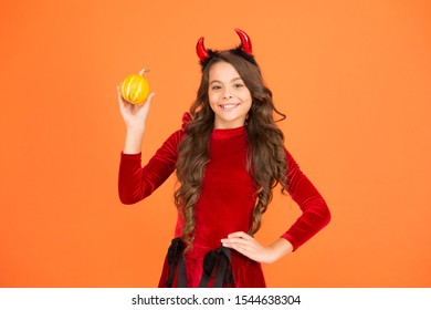 Pumpkin carving and ghost hunting. Halloween party child. Happy child hold pumpkin orange background. Little child wear red devil horns. Halloween look of small child girl. Holiday celebration.