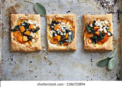 Pumpkin, chard, goat cheese and pine nuts puff pastry tarts. Overhead view.
