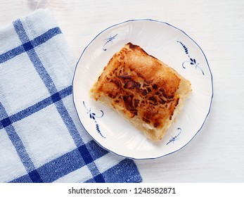 Pumpkin and cheese strudel, traditional Croatian snack called bucnica on white wooden table. Top view.