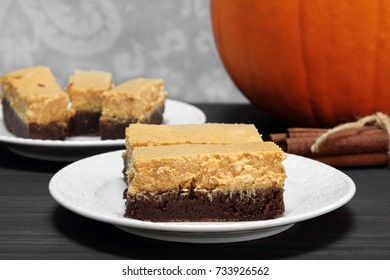 Pumpkin cheesecake brownie bars.  Great addition to the holiday table for Thanksgiving or a Halloween celebration.