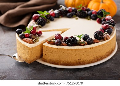 Pumpkin cheesecake with sour cream topping and fresh seasonal berries and nuts with a slice taken out