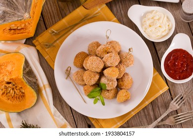 Pumpkin chicken meatballs with carrot on white dish.