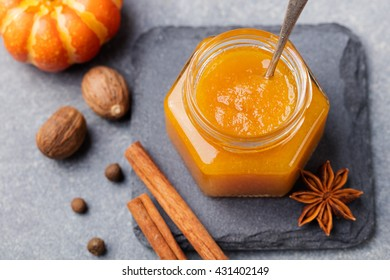 Pumpkin confiture, jam, sauce with spices on stone table Top view