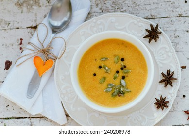 Pumpkin cream soup in a bowl  on a vintage plate with seeds and spices
