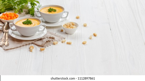 Pumpkin cream soup with croutons, raw fresh pumpkin pieces and herbs on a white rustic wooden background, Autumn concept.