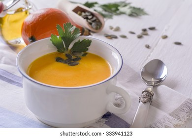 Pumpkin cream soup with ginger and parsley on white table background.Selective focus.