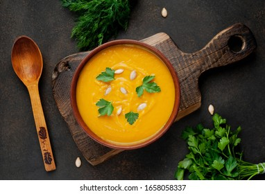 pumpkin cream soup with seeds and herbs on a stone background. healthy food.