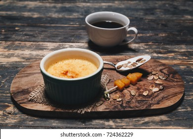 Pumpkin creme brûlée on wooden background. Dessert with pumpkin seeds, dried apricot and cup of coffee on wooden background