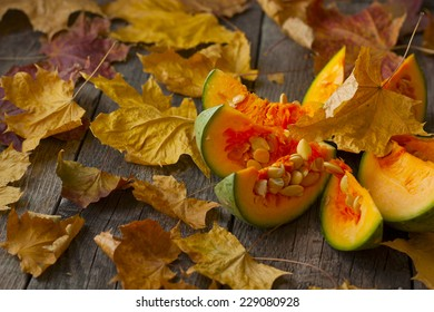 pumpkin, cut into pieces on a wooden background strewn with autumn leaves