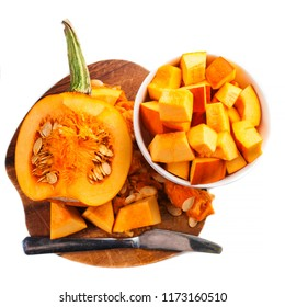 Pumpkin cut in a pieces on wooden cutting board   isolated on white background. Diced Pumpkin. Thanksgiving day or seasonal autumnal concept
