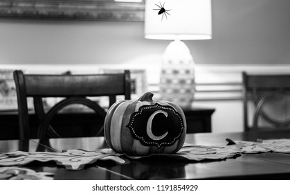 Pumpkin decoration with the letter C in center as a centerpiece for fall decorations and spider hanging down in black and white