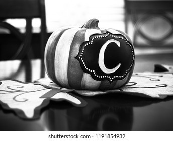 Pumpkin decoration with the letter C in center as a centerpiece for fall decorations up close