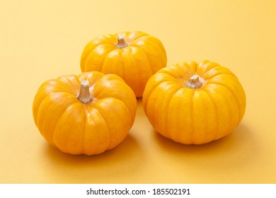 Pumpkin decorations for Halloween on yellow background