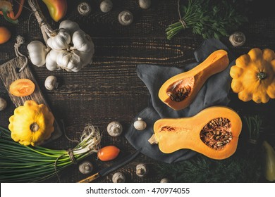 Pumpkin with different vegetables on the old wooden table