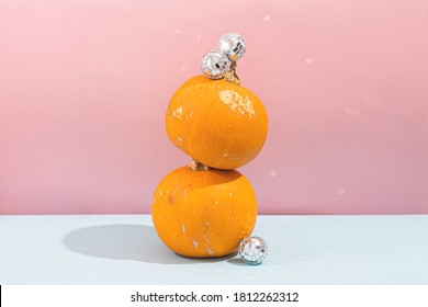 Pumpkin with disco ball on pink blue background. Halloween party