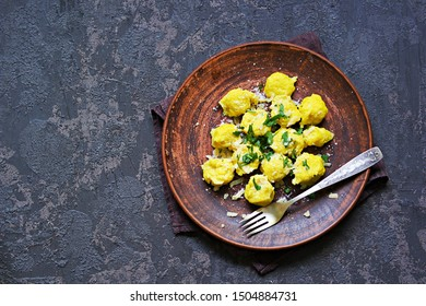 Pumpkin dumplings or gnocchi with parmesan cheese, butter and parsley on a brown clay plate. Harvest pumpkins. Thanksgiving Day. Top view, copy space. Italian food.