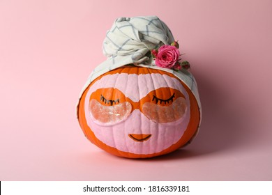 Pumpkin with eye patches and towel on pink background