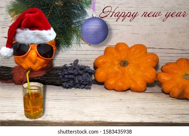 pumpkin in glasses drinking juice from a tube, on a wooden white Board with a pine branch and congratulations on the new year