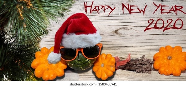 pumpkin in glasses, on a wooden white Board with a pine branch and a happy new year 2020