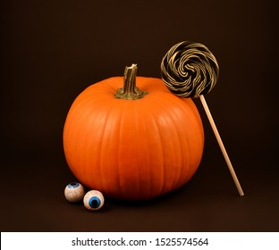 Pumpkin with halloween candy stock images. Halloween lollipops and chocolate eyes stock images. Sweet halloween food. Scary halloween chocolate eyes. Pumpkin on a dark background