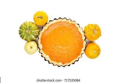 pumpkin homemade pie arranged with small pumpkins isolated on white background top view