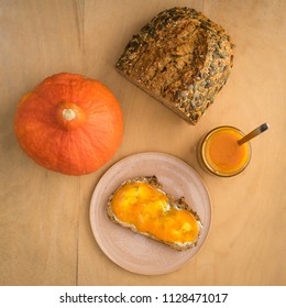 Pumpkin jam in a jar with fresh wholegrain bread and butter