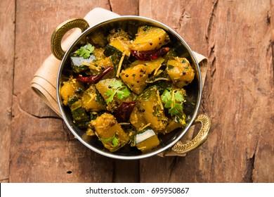 Pumpkin OR Kaddu ki Sabzi served in a bowl over moody background, selective focus