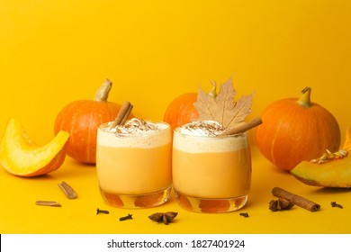 Pumpkin latte drink. Autumn coffee with spicy pumpkin flavor and cream on a yellow background. Seasonal Fall Drinks for Halloween and Thanksgiving