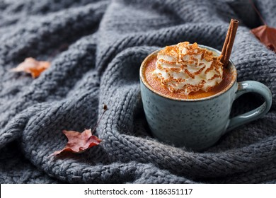 Pumpkin latte with spices. Boozy cocktail with whipped cream. Grey knitted background. Copy space.