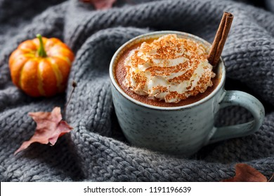 Pumpkin latte with spices. Boozy cocktail with whipped cream. Grey knitted background. Close up.
