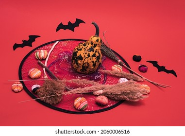 Pumpkin, little fabric pumpkinks and fabric bats standing on witch´s hat. Funny Halloween minimal gothic decoration concept on pastel red background