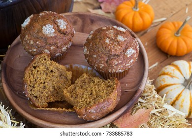 Pumpkin muffins on a wooden plate with pumpkins in background