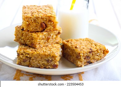 Pumpkin and oat bars with raisin and bottle of milk, selective focus