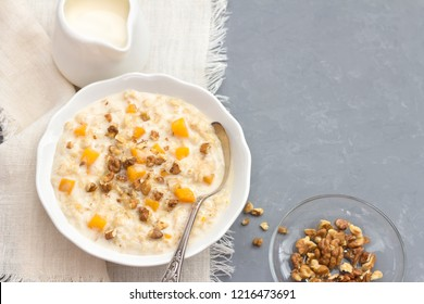 Pumpkin oatmeal with honey and nuts, milk in a milkman, walnuts on a gray background. healthy delicious homemade breakfast. free space