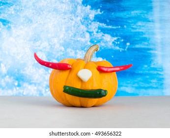 pumpkin on water background, red chili in pumpkin, yellow pumpkin make mouth by green chili, garlic on yellow pumpkin,