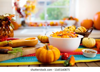 Pumpkin, onion and carrot ready for cooking of soup for autumn meal. Healthy fall vegetables for Halloween season lunch. Squash cut on wooden table in sunny kitchen.