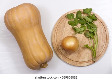Pumpkin, onion, cilantro and a cutting board on a white background