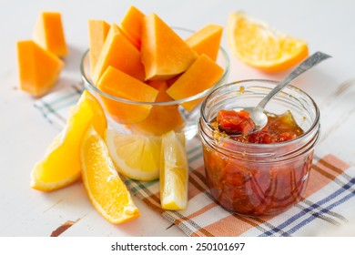 Pumpkin and orange jam in glass jar with ingredients on white wood background